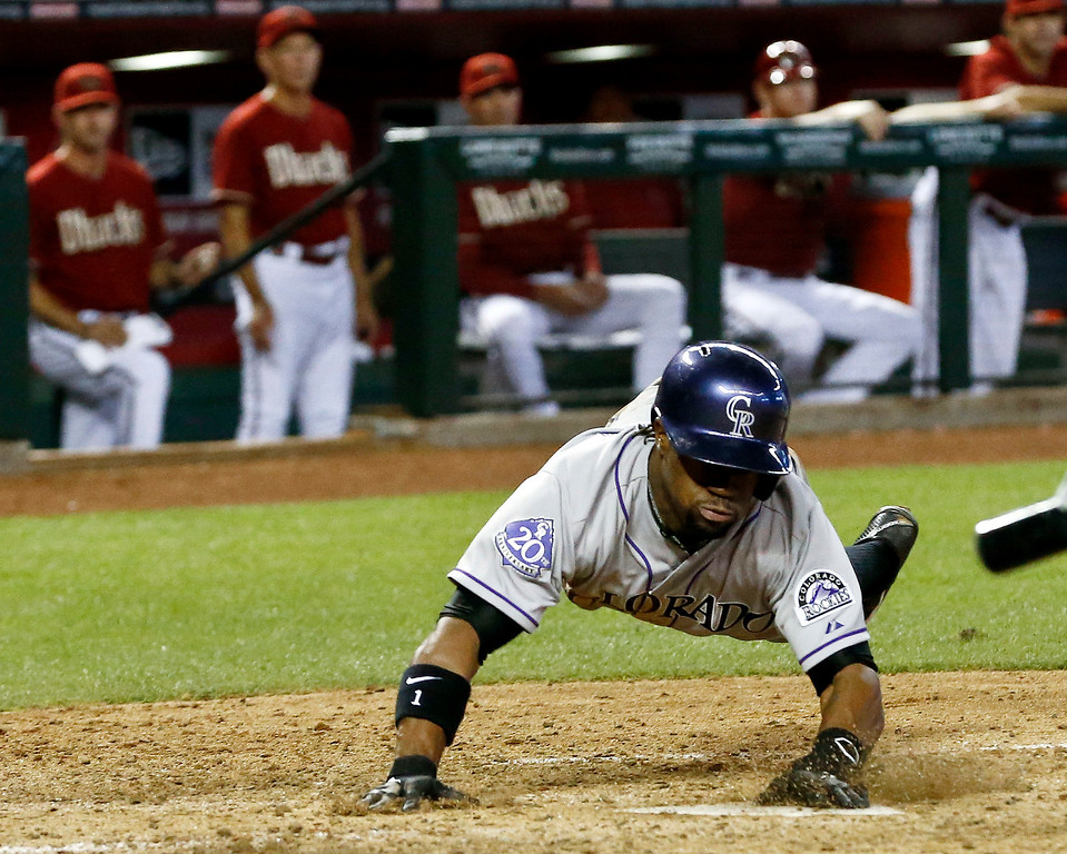 . Colorado Rockies\' Eric Young Jr. slides in to score a run at the Arizona Diamondbacks players on the bench watch the action during the sixth inning of a baseball game, on Sunday, April 28, 2013, in Phoenix. (AP Photo/Ross D. Franklin)