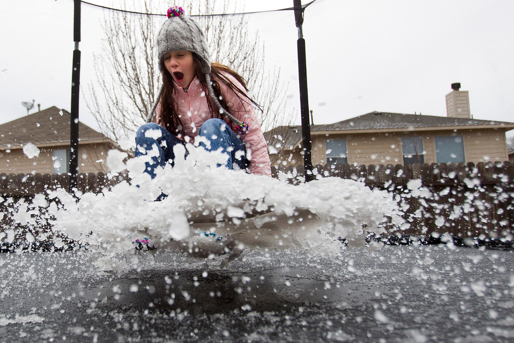 . Eryn Garza bounces on a slush-covered trampoline from an overnight sleet storm Tuesday, Jan. 28, 2014, in Spring, Texas.(AP Photo/Houston Chronicle, Brett Coomer)