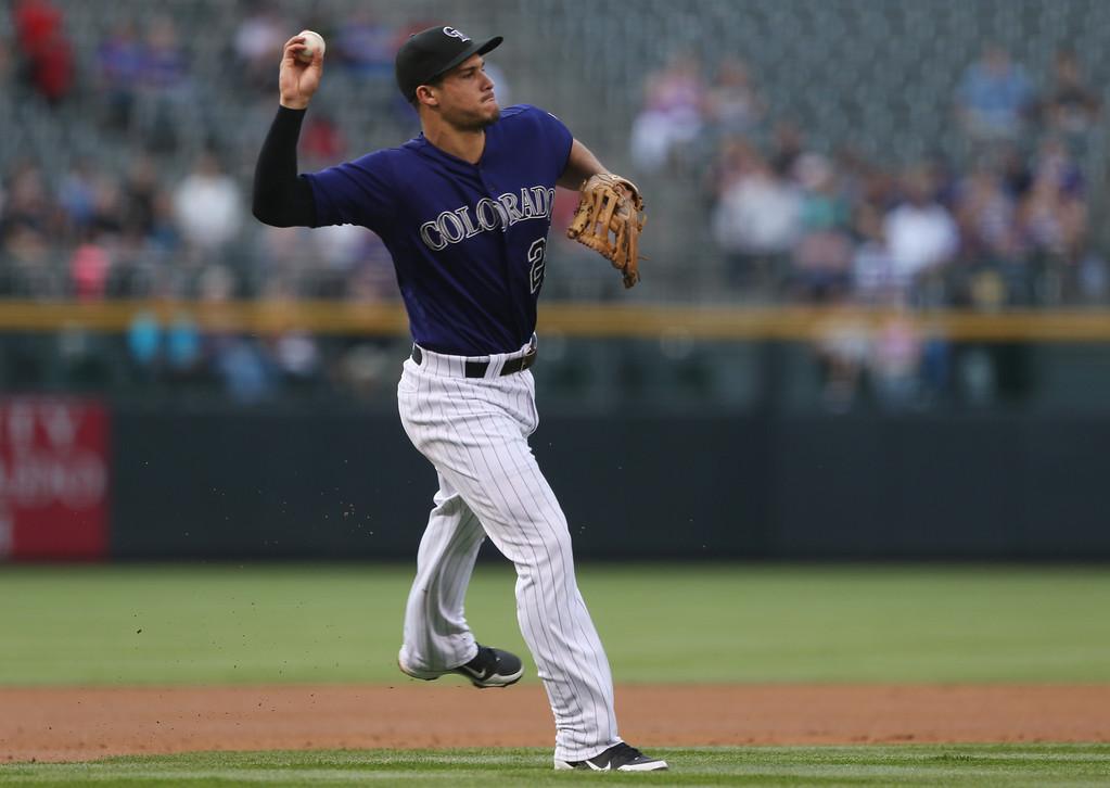 . Colorado Rockies third baseman Nolan Arenado throws to first base to put out Texas Rangers\' Josh Wilson in the first inning of an interleague baseball game in Denver on Monday, May 5, 2014. (AP Photo/David Zalubowski)
