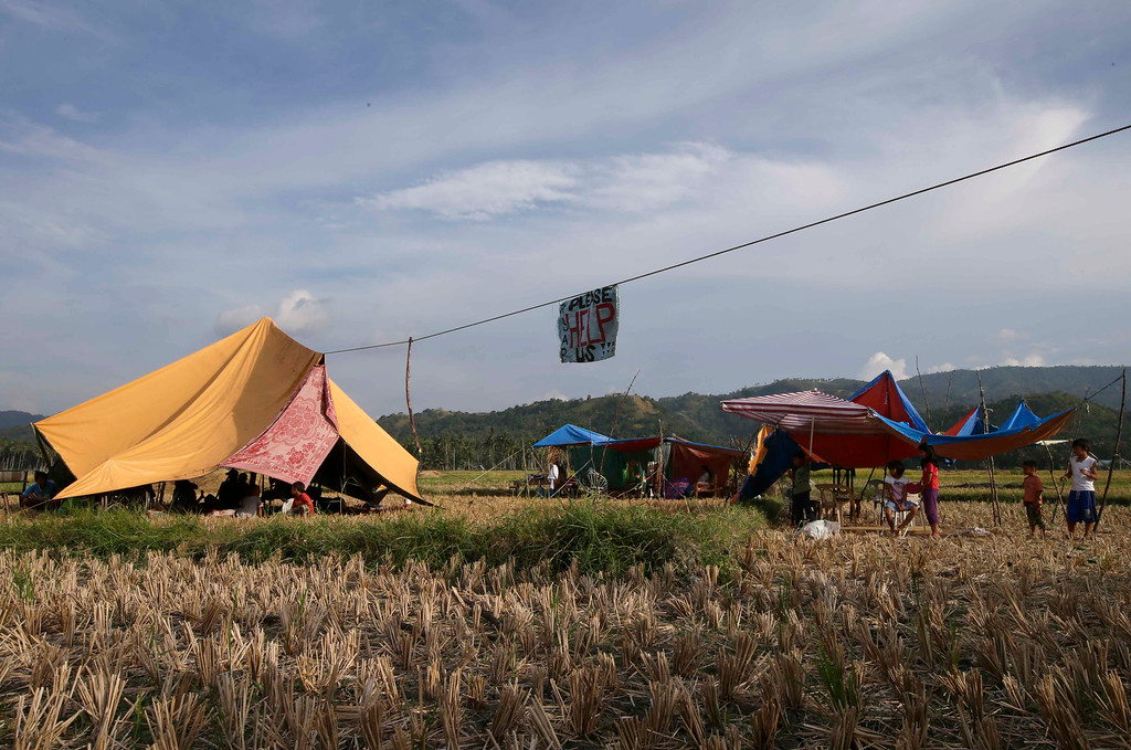 ". People display a message ""Please Help Us\"" as they camp out in the middle of a rice field to avoid aftershocks at Calape township, Bohol province in central Philippines, Wednesday Oct. 16, 2013. (AP Photo/Bullit Marquez)"