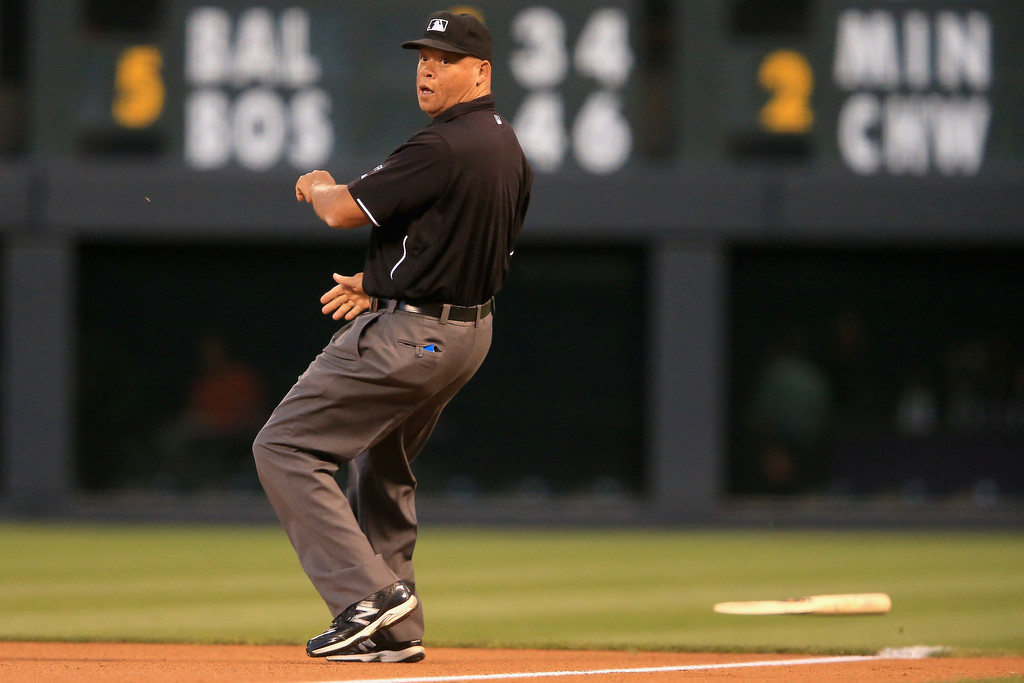 . First base umpire Kerwin Danley avoids the broken bat of Corey Dickerson #6 of the Colorado Rockies as he leads off against the St. Louis Cardinals in the first inning at Coors Field on September 17, 2013 in Denver, Colorado.  (Photo by Doug Pensinger/Getty Images)