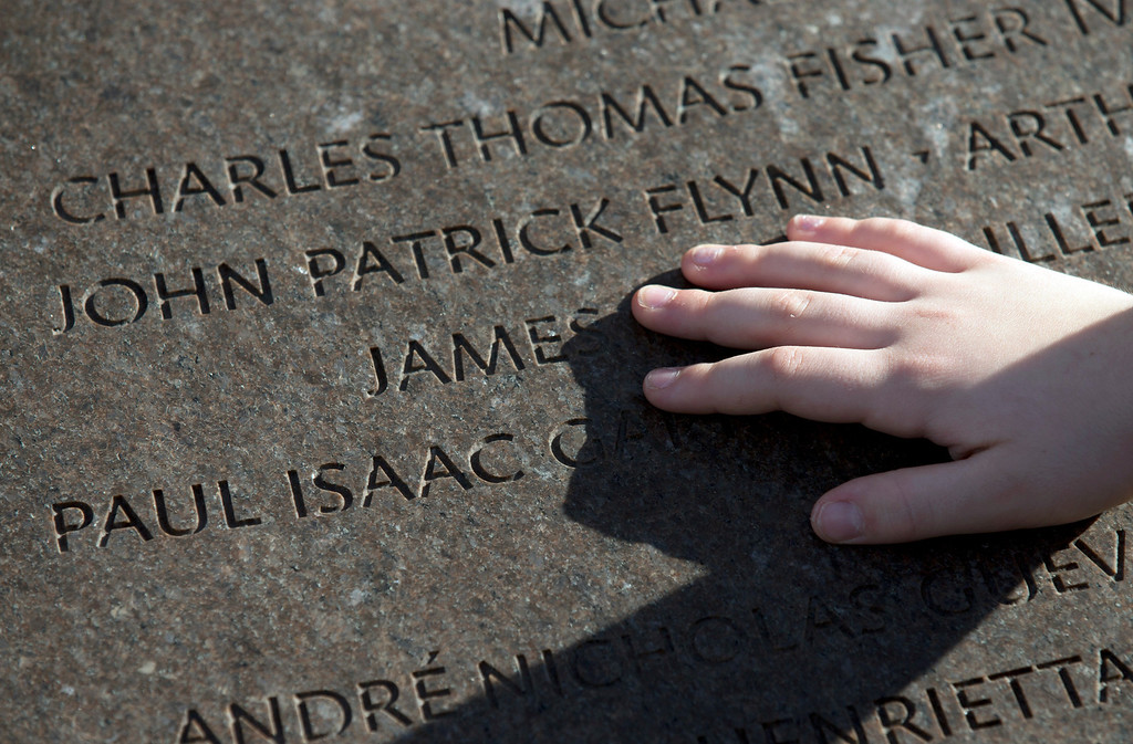 . Hedda Flynn, 8, touches the Pan Am Flight 103 memorial cairn at Arlington National Cemetery, in Arlington, Va., Saturday, Dec. 21, 2013, bearing his uncleís name John Patrick Flynn, who just turned 22 at the time of the crash, during a memorial service to mark the 25th anniversary of the bombing of the Pan Am Flight 103 that crashed over Lockerbie, Scotland.  (AP Photo/Manuel Balce Ceneta)