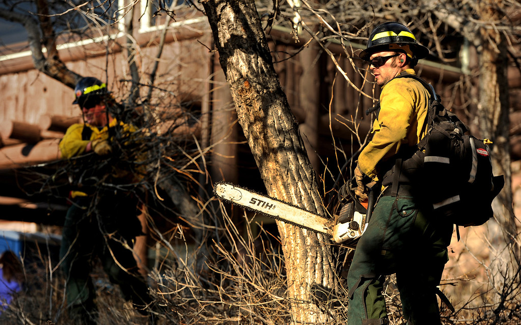 . Wildland firefighters Chris Wetzel, left and Mitch Sprague, right,  from Lafayette Fire,  clear brush and debris from the Moraine Park Vistor\'s Center to protect the structure just in case the fire reaches the building on December 2nd, 2012. The Fern Lake Fire, which has been burning in Rocky Mountain National Park since October, kicked up yesterday and forced the evacuation of hundreds of homes east of the fire. Helen H. Richardson, The Denver Post