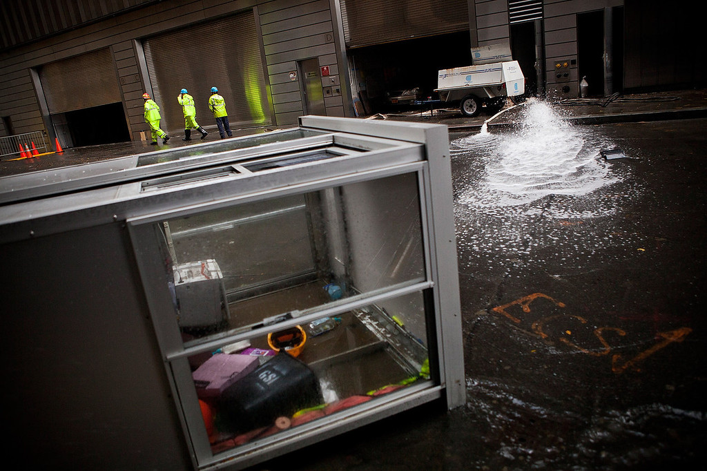 . Con Edison employees monitor the drainage of water being pumped out of Seven World Trade Center, caused by Hurricane Sandy, on October 30, 2012 in the Financial District of New York, United States. The storm has claimed at least 33 lives in the United States, and has caused massive flooding across much of the Atlantic seaboard.  (Photo by Andrew Burton/Getty Images)