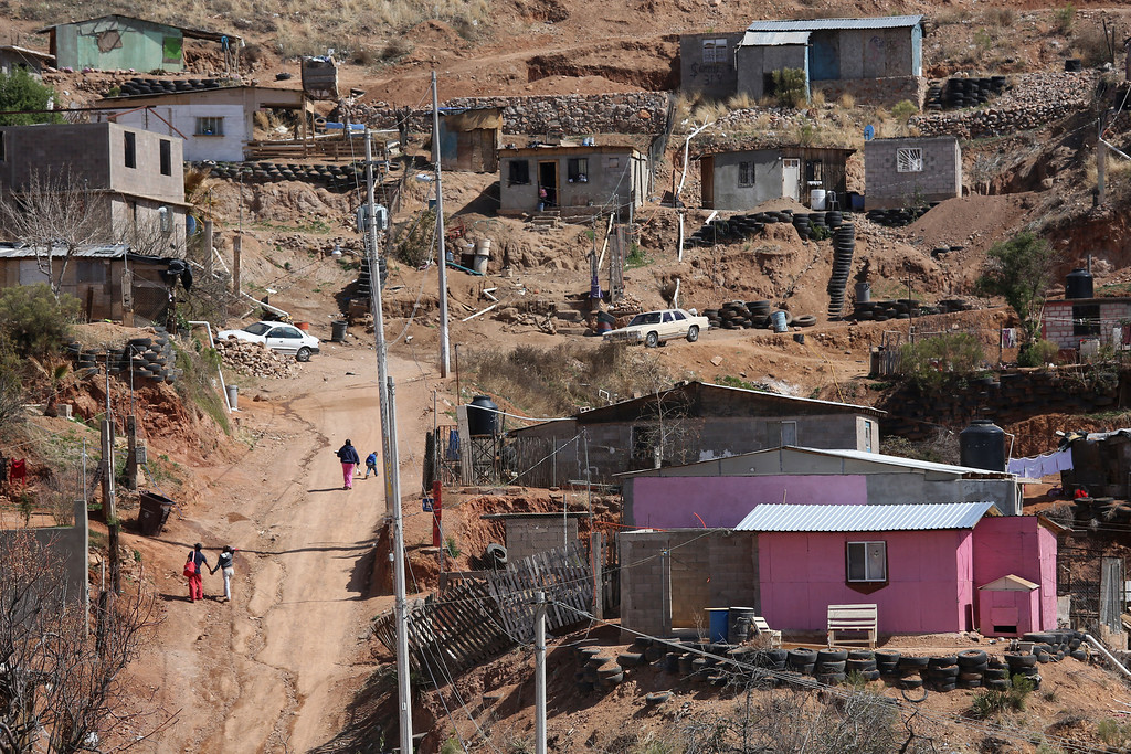 . NOGALES, MEXICO - MARCH 05:  People walk past homes near the Tirabichi garbage dump on March 5, 2013 in Nogales, Mexico. About 30 families live inside the Tirabichi garbage dump, searching for recyclables to sell for a living.  (Photo by John Moore/Getty Images)