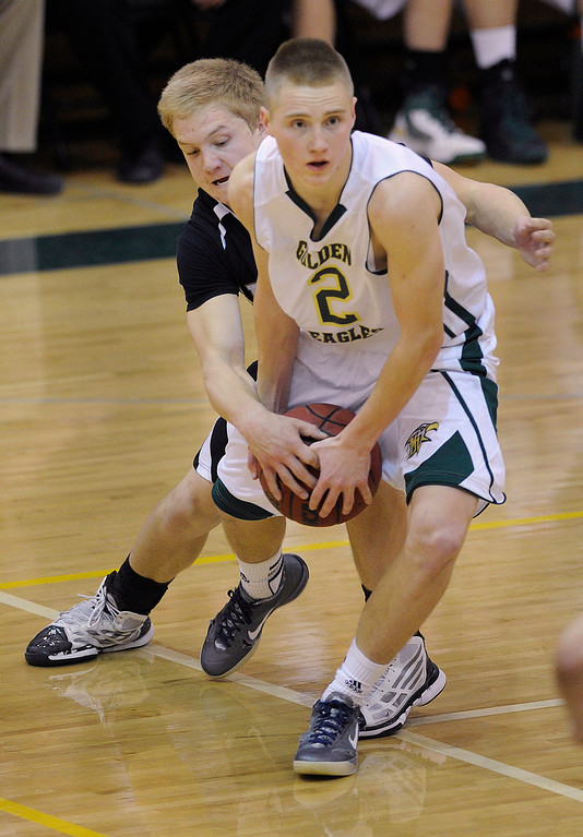 . Arapahoe guard Blake Nelson (5) tried to tie up Mountain Vista\'s Chandler Wiscombe (2) in the second half. The Mountain Vista High School boy\'s basketball team defeated Arapahoe 69-54 Friday night January 4, 2013.  Karl Gehring/The Denver Post