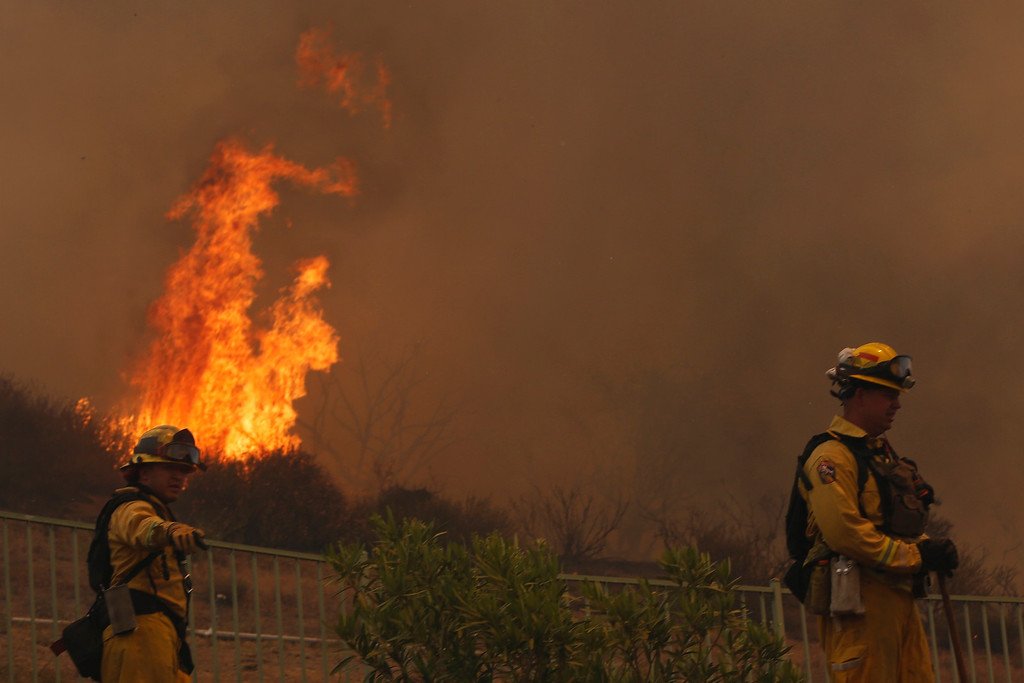 . Firefighters work to protect homes from a fast-moving brush fire in the Newbury Park area of Ventura County May 2, 2013.  REUTER/Patrick T. Fallon