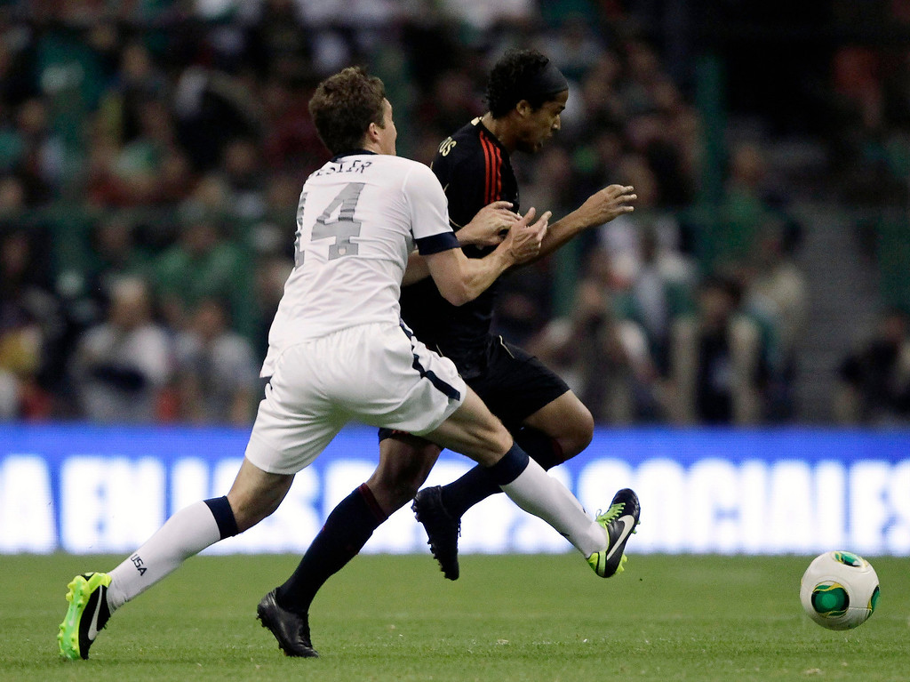. Matt Besler (L) of the U.S battles for the ball with Mexico\'s Giovani Dos Santos during their 2014 World Cup qualifying soccer match at Azteca stadium in Mexico City March 26, 2013.REUTERS/Henry Romero