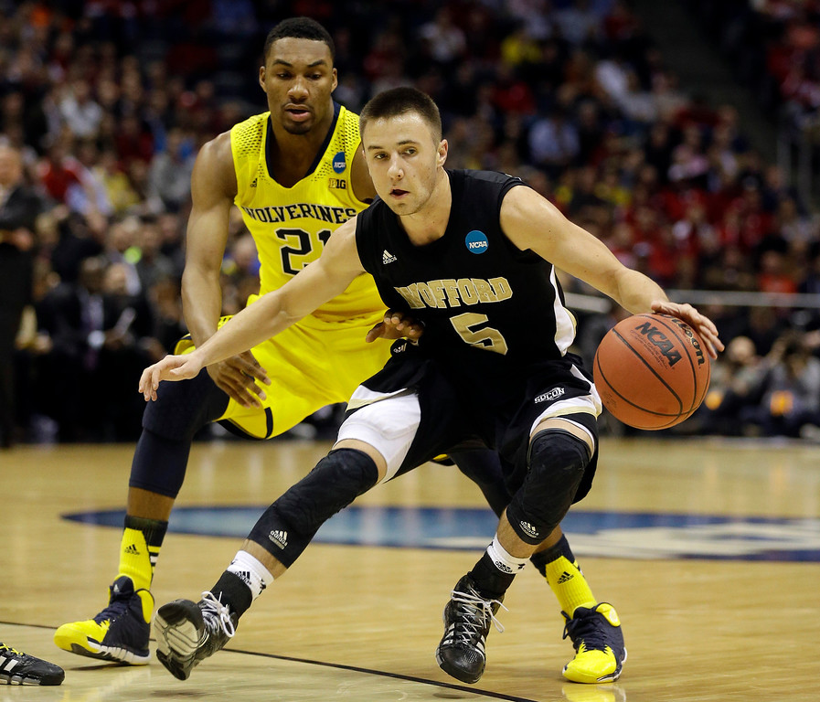 . Wofford guard Eric Garcia (5) drives the ball against Michigan guard Zak Irvin (21) during the first half of a second round NCAA college basketball tournament game Thursday, March 20, 2014, in Milwaukee. (AP Photo/Jeffrey Phelps)