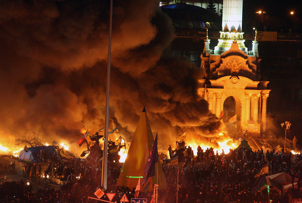 . Smoke from exploding fireworks and fires billows into the night sky as Ukrainians gather on the Independence Square during continuing protest in Kiev, Ukraine, 18 February 2014.   EPA/IGOR KOVALENKO