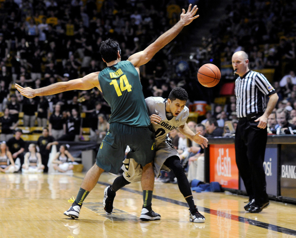 . BOULDER, CO. - MARCH 7: Oregon forward Arsalan Kazemi (14) put a road block up in front of Colorado guard Askia Booker (0) in the second half. The University of Colorado men\'s basketball team defeated Oregon 76-53 Thursday night, March 7, 2013 at the CU Events Center in Boulder. (Photo By Karl Gehring/The Denver Post)
