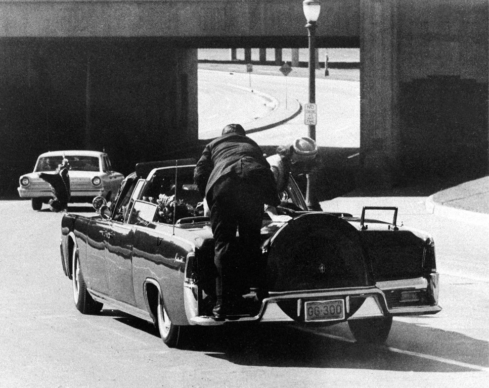 . Jacqueline Kennedy leans over the president who slumps in the back seat of limousine as it speeds toward the Stemmons Freeway. Secret Service agent Clinton Hill rides on the back of the car.  James W. Altgenss, Associated Press file