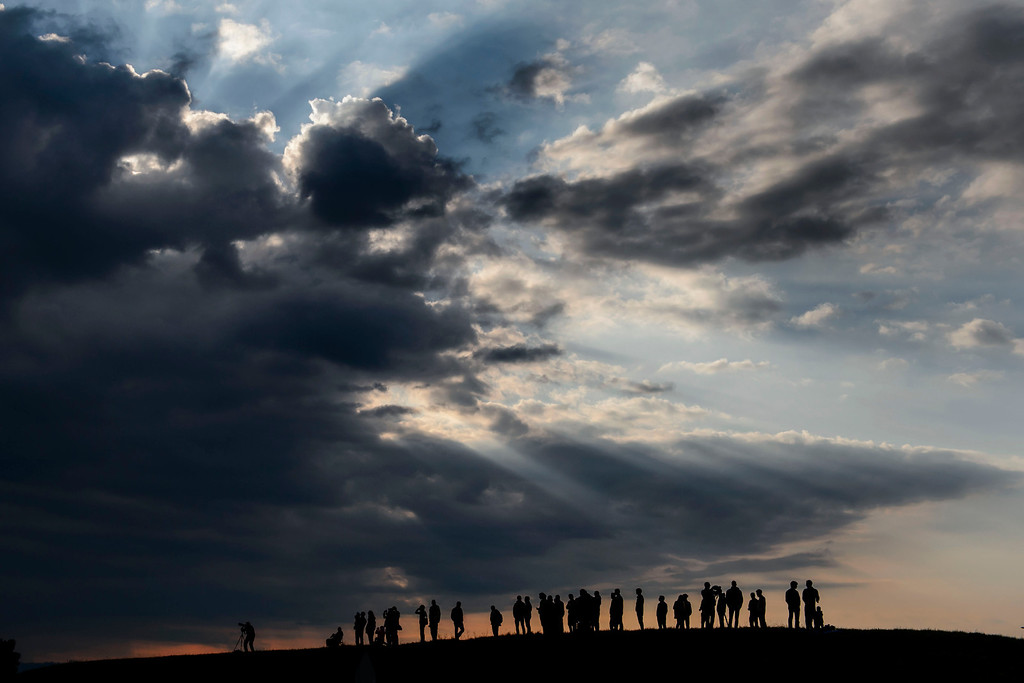 . Spectators watch under heavy clouds the a landing of  solar-powered Solar Impulse 2 aircraft  after its first flight on Monday  June 2, 2014 in Payerne, Switzerland. (AP Photo/Fabrice Coffrini,Pool)