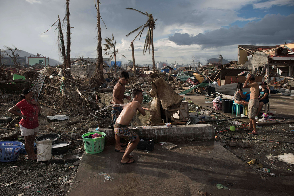 . Typhoon survivors take a shower and wash their clothes in Palo on November 21, 2013. The United Nations has confirmed at least 4,500 killed in the disaster, which brought five-meter (16-foot) waves to Tacloban, flattening nearly everything in their path as they swept hundreds of meters across the low-lying land. AFP PHOTO/ Nicolas ASFOURI/AFP/Getty Images