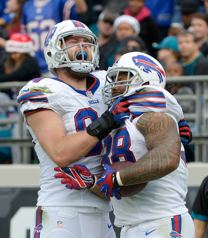 . Buffalo Bills tight end Scott Chandler (84) celebrates with fullback Frank Summers, right, after Summers caught a 1-yard touchdown pass against the Jacksonville Jaguars during the second half of an NFL football game in Jacksonville, Fla., Sunday, Dec. 15, 2013.(AP Photo/Phelan M. Ebenhack)