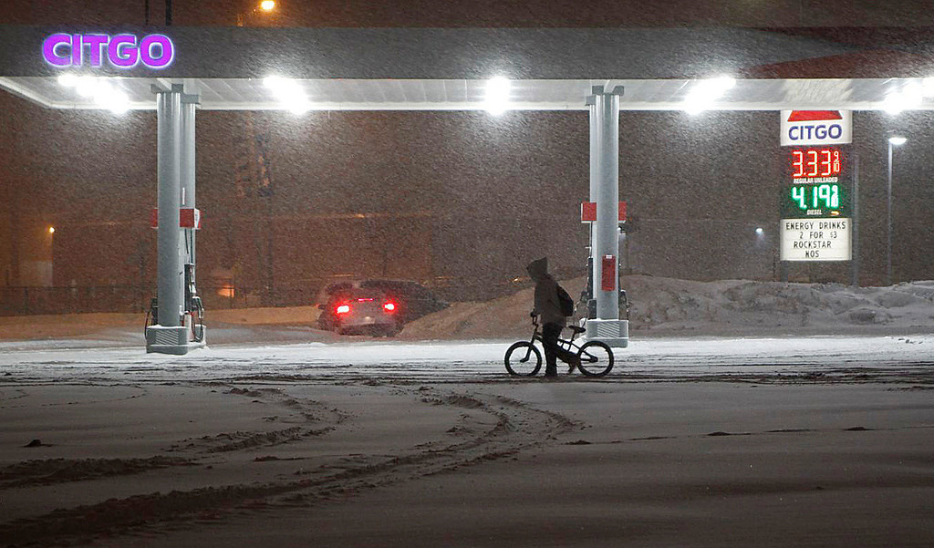 . A bicyclist walks his bike by a gas station early Wednesday, on a snowy morning Feb. 5, 2014, in Battle  Creek, Mich.  on snowy Wednesday morning.  Totals of 5 to 8 inches are expected in several Michigan counties.  (AP Photo/The Enquirer, David Smith)