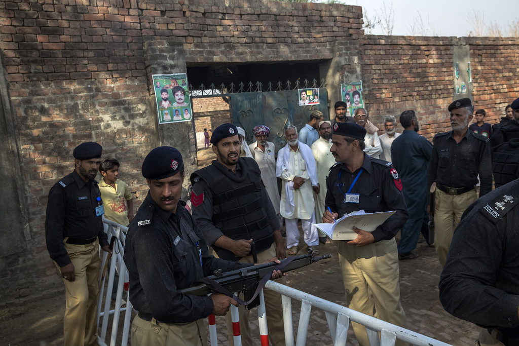 . LAHORE, PAKISTAN - MAY 11: Police provide security at a polling station as people queue to cast their ballot prior to opening on May 11, 2013 on the outskirts of Lahore, Pakistan. Millions of Pakistanis cast their votes in parliamentary elections held today on May 11. It is the first time in the country\'s history that an elected government will hand over power to another elected government.  (Photo by Daniel Berehulak/Getty Images)
