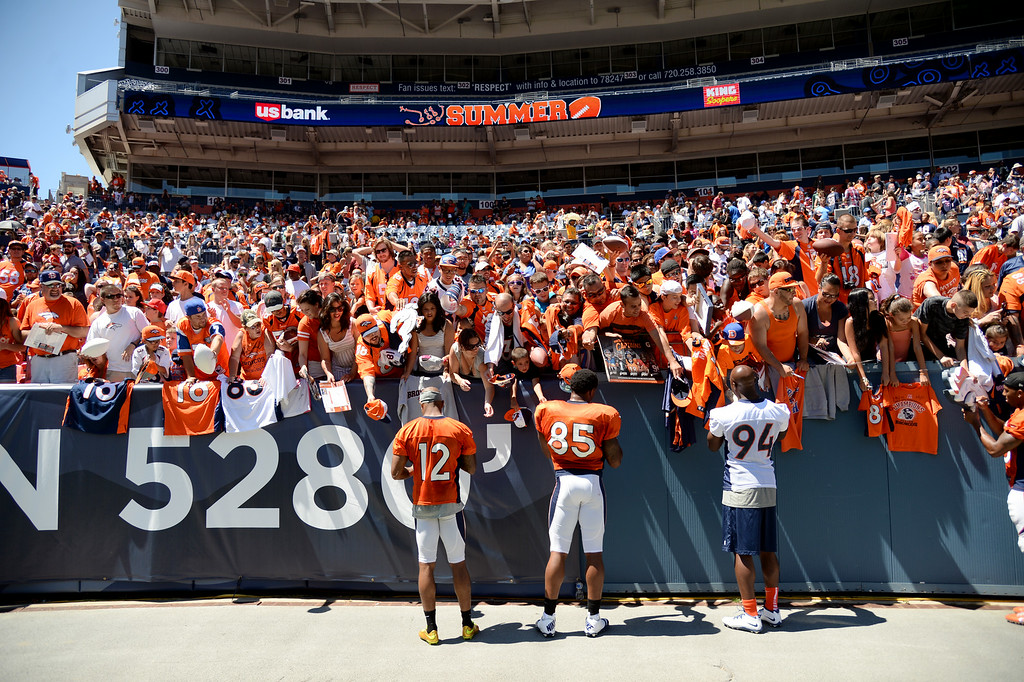 . Andre Caldwell (12), Derek Wolfe (95) and DeMarcus Ware of Denver Broncos are signning autographs for the fans  after the Broncos scrimmage at Sports Authority Field at Mile High. Denver, Colorado. August 02. 2014. (Photo by Hyoung Chang/The Denver Post)