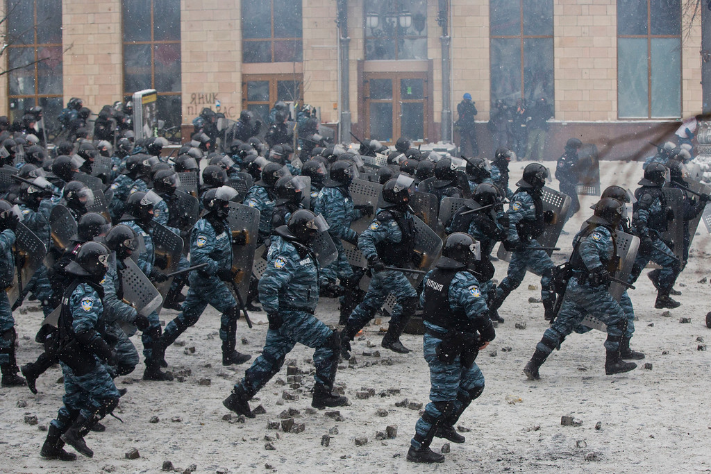 . Helmeted riot police move in on hundreds of protesters in central Kiev, Ukraine, Wednesday, Jan. 22, 2014. Two people whose dead bodies were found Wednesday near the site of clashes with police have been shot with live ammunition, prosecutors said Wednesday, an announcement that could further fuel violence that spilled on the streets of the Ukrainian capital after two months of largely peaceful protests. (AP Photo/Evgeny Feldman)
