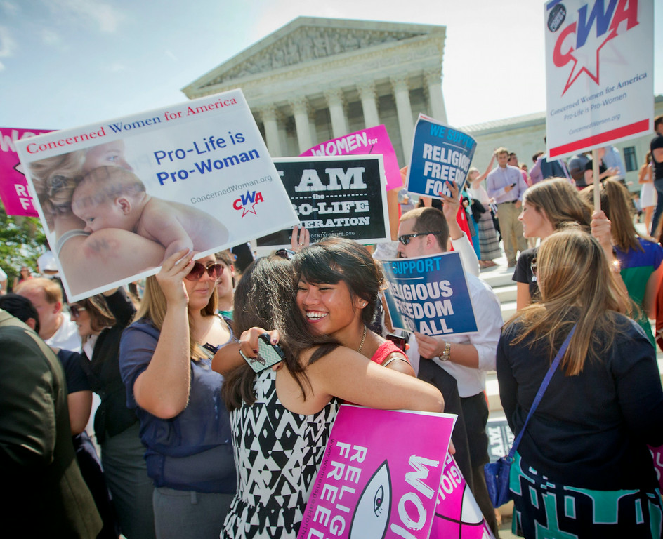 . Demonstrators embrace as they react to hearing the Supreme Court\'s decision on the Hobby Lobby case outside the Supreme Court in Washington, Monday, June 30, 2014. The Supreme Court says corporations can hold religious objections that allow them to opt out of the new health law requirement that they cover contraceptives for women.(AP Photo/Pablo Martinez Monsivais)
