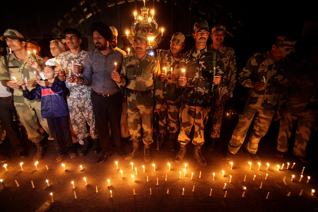 . Indian Border Security Force soldiers and villagers light candles to celebrate Diwali, near the India-Pakistan international border area, at Ranbir Singh Pora, about 33 kilometers (21 miles) from Jammu, India, Saturday, Nov. 2, 2013. Diwali, the Hindu festival of colors, will be celebrated on Sunday. (AP Photo/Channi Anand)