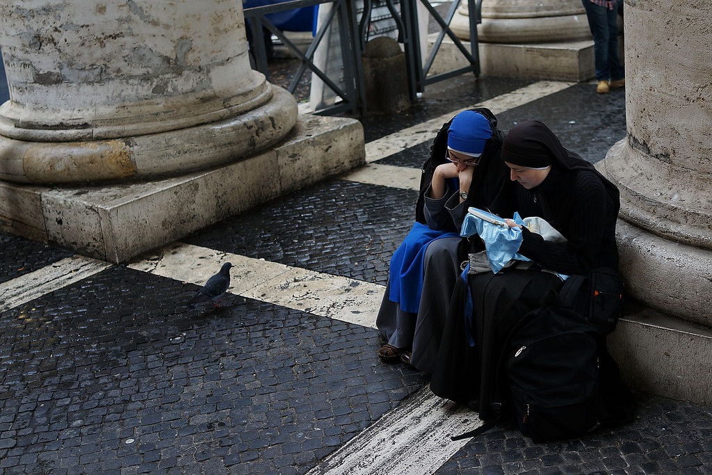 . Two nuns sit in St. Peter\'s Square on March 12, 2013 in Vatican City, Vatican. Pope Benedict XVI\'s successor is being chosen by the College of Cardinals in Conclave in the Sistine Chapel. (Photo by Spencer Platt/Getty Images)