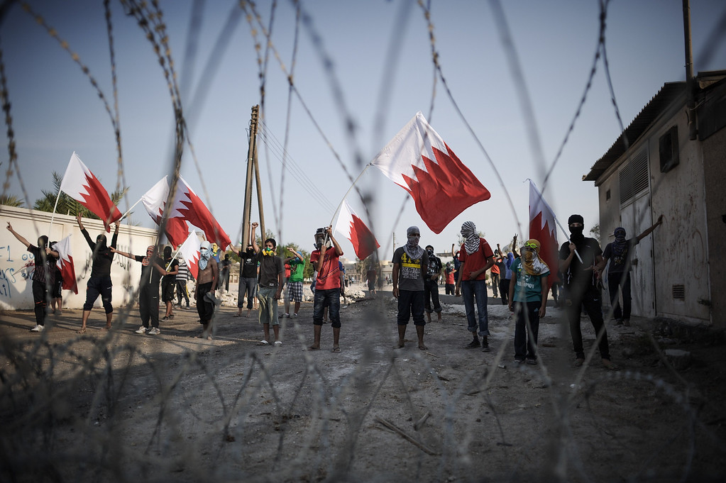 . Bahraini protestors wave their national flag as they stand behind barbed wire placed by riot police during demonstration against the ruling regime in the village of Shakhora, west of Manama, on August 14, 2013.. Bahraini police headed off a protest against Gulf kingdom\'s Sunni rulers that the Shiite-led opposition activists called for near the US embassy in defiance of a ban. The police deployment prevented protesters from reaching the spot designated by the Bahrain Rebellion Movement, Tamarod, for the main rally outside the US embassy in the capital Manama. MOHAMMED AL-SHAIKH/AFP/Getty Images