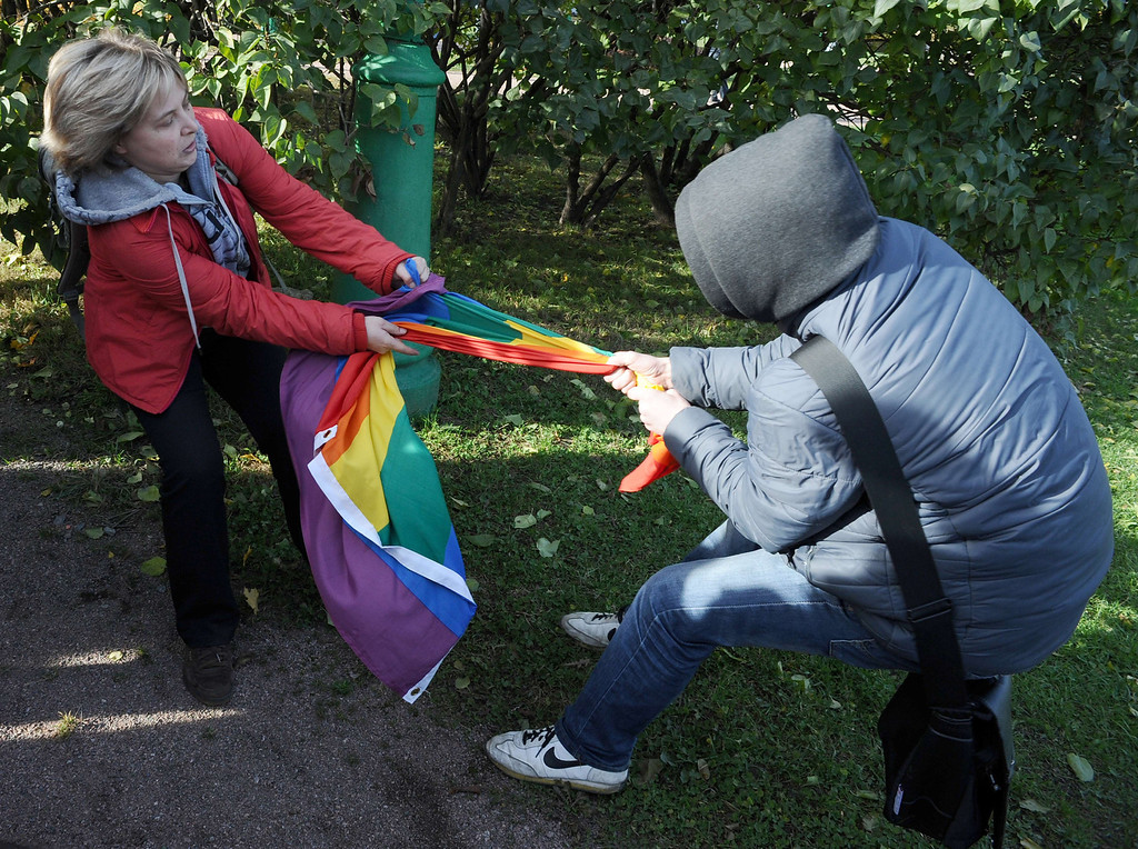 . A gay rights activist (L) fights for her rainbow flag against an anti-gay protester during a gay pride event in Saint Petersburg on October 12, 2013. Russian police arrested today in the city of Saint Petersburg several people after clashes erupted between pro- and anti-gay demonstrators. OLGA MALTSEVA/AFP/Getty Images