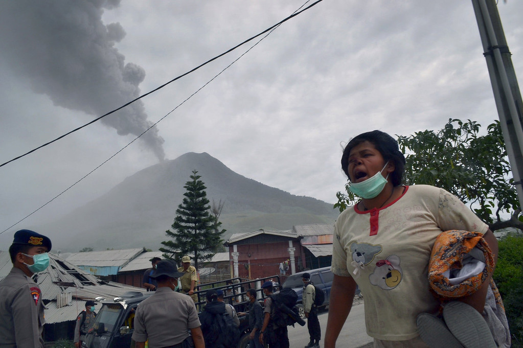 . Indonesian police evacuate residents of Karo district from the erupting Mount Sinabung volcano on September 17, 2013. Thousands of villagers fled after Mount Sinabung\'s series of volcanic eruptions on Indonesia\'s Sumatra island, spewing rocks and red-hot ash onto surrounding villages, officials said.   SUTANTA ADITYA/AFP/Getty Images