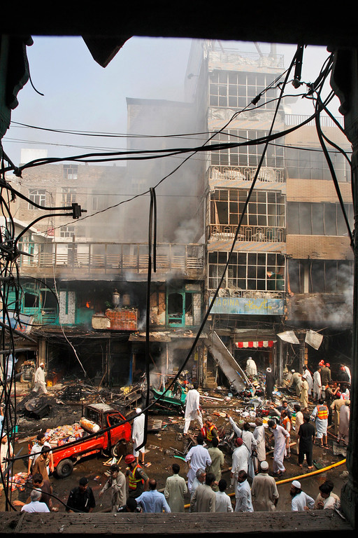 . Pakistani rescue workers, police officers and civilians gather at the site of a car bomb explosion in Peshawar, Pakistan, Sunday, Sept. 29, 2013.  (AP Photo/Mohammad Sajjad)