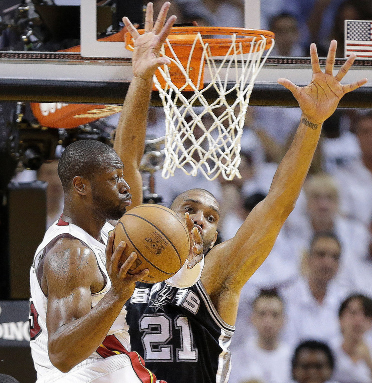. Miami Heat shooting guard Dwyane Wade (3) looks to pass under pressure from San Antonio Spurs power forward Tim Duncan (21) during the first half of Game 1 of basketball\'s NBA Finals, Thursday, June 6, 2013 in Miami. (AP Photo/Lynne Sladky)