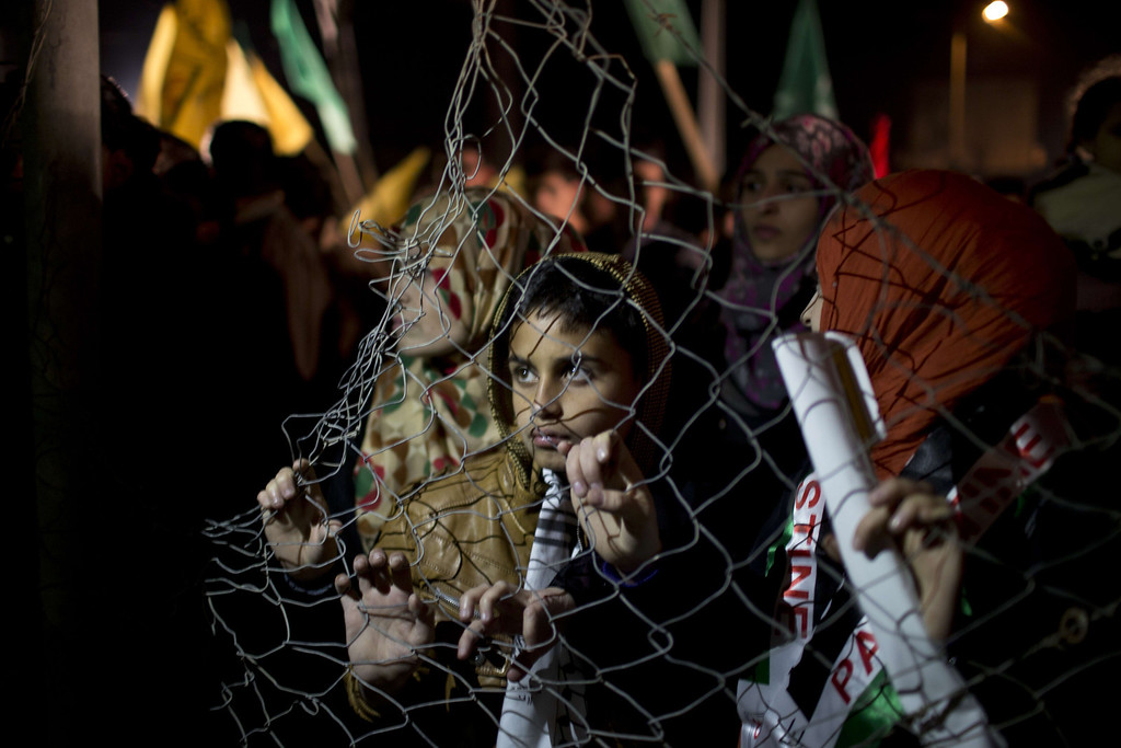 . Palestinian prisoners\' relatives wait behind a fence for their release at Erez point in the northern Gaza Strip on October 29, 2013. Israel was preparing on October 29, 2013 to release 26 long-serving Palestinian prisoners, the second batch of 104 inmates who are to be freed in line with commitments to US-brokered peace talks. The release, due to take place late at night, will see 21 prisoners going to their homes in the West Bank.  MAHMUD HAMS/AFP/Getty Images