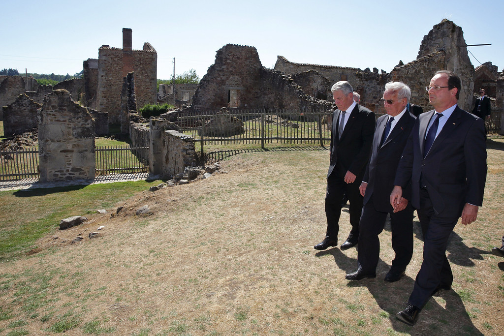 . From right, France\'s President Francois Hollande, Robert Hebras, 88,  one of the last survivors of the World War II Oradour-sur-Glane\'s massacre,  and German President Joachim Gauck, walk in the streets of the French martyr village of Oradour-sur-Glane, southwestern France, Wednesday, Sept. 4, 2013. Holding hands in quiet tribute, the presidents of Germany and France visited the scene of the largest massacre in Nazi-occupied France nearly seven decades ago. Wednesday\'s visit by German President Joachim Gauck to the southwestern French town of Oradour-sur-Glane is the first by a serving German leader. (AP Photo/ Phillipe Wojazer, Pool)