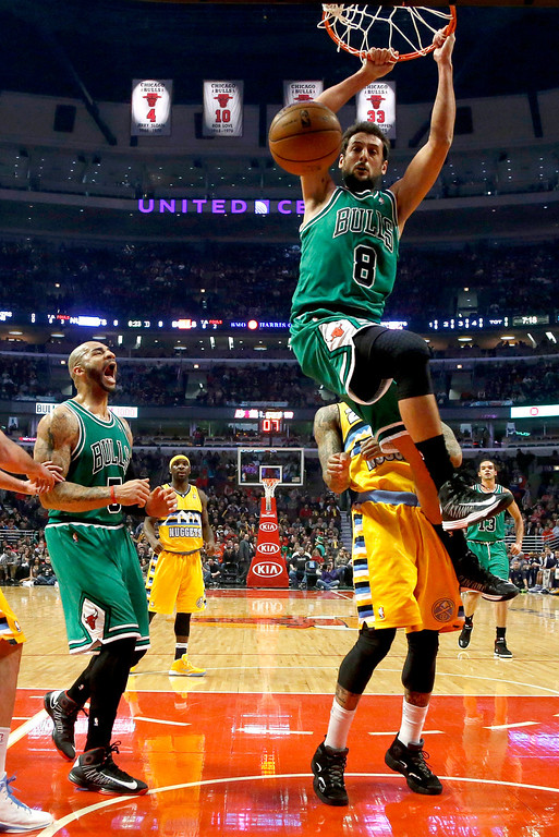 . Chicago Bulls guard Marco Belinelli (8) dunks over Denver Nuggets guard Wilson Chandler as Bulls\' Carlos Boozer (5) watches during the first half of an NBA basketball game, Monday, March 18, 2013, in Chicago. (AP Photo/Charles Rex Arbogast)