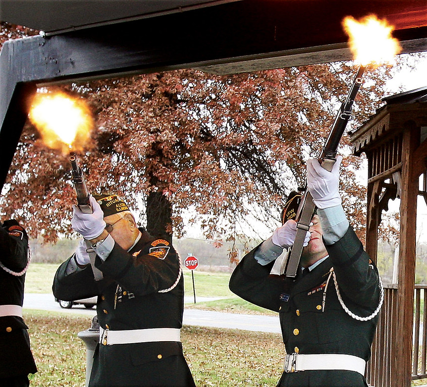 . Flames erupt from the barrels of the M1 Garand rifles of the Alton VFW Post 1308 Ritual Team Monday, Nov. 11, 2013, during the volley salute just before the playing of Taps to end the annual Veterans Day observance ceremony at the post in Alton, Ill. Visitors listened to a proclamation from the mayor of Alton which was followed by the placing of wreaths from several organizations and branches of the U.S. military.  (AP Photo/The Telegraph,John Badman)