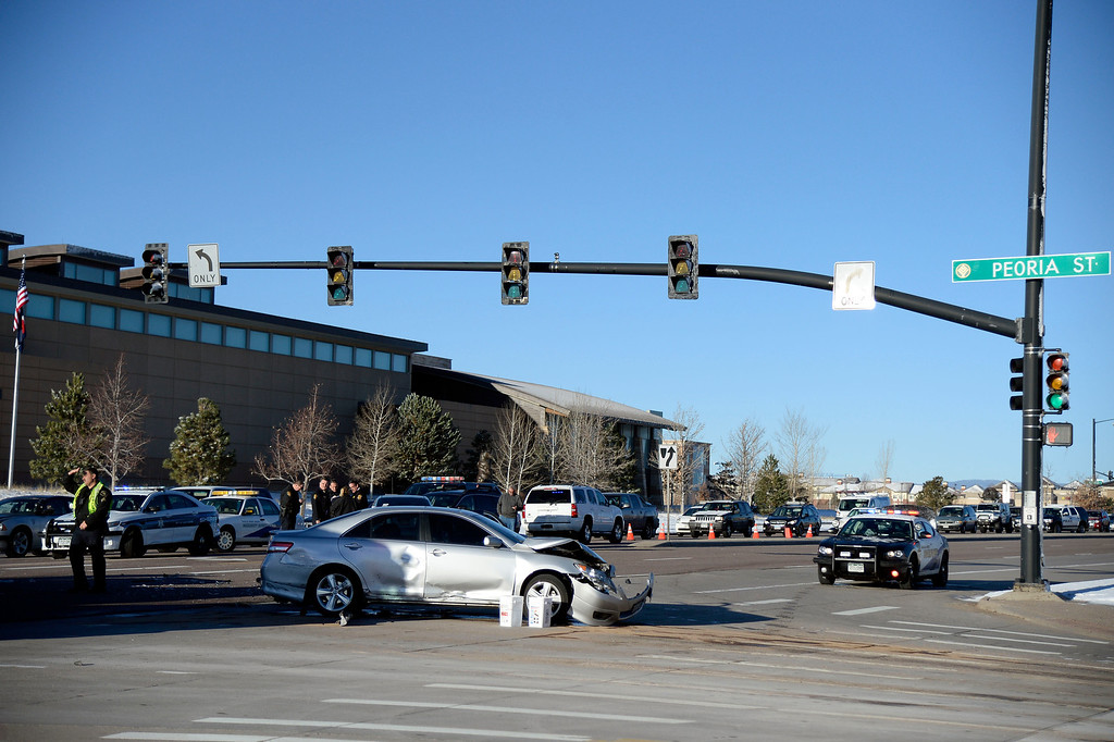 . The car a suspect car jacked ended up at the intersection of Peoria and Lincoln. Suspect in a car jacking starting in Longmont came to an end in Douglas County March 12, 2014 where he ran into several cars, jumping out and was apprehended behind a Wells Fargo Bank in a strip mall at Lincoln and Peoria.  (Photo by John Leyba/The Denver Post)