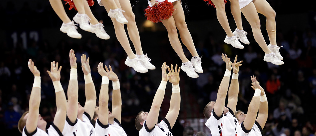 . Cincinnati cheerleaders reach to catch other cheerleaders after tossing them into the air during a timeout in the second half during the second round of the NCAA men\'s college basketball tournament in Spokane, Wash., Thursday, March 20, 2014. Harvard won 61-57. (AP Photo/Elaine Thompson)
