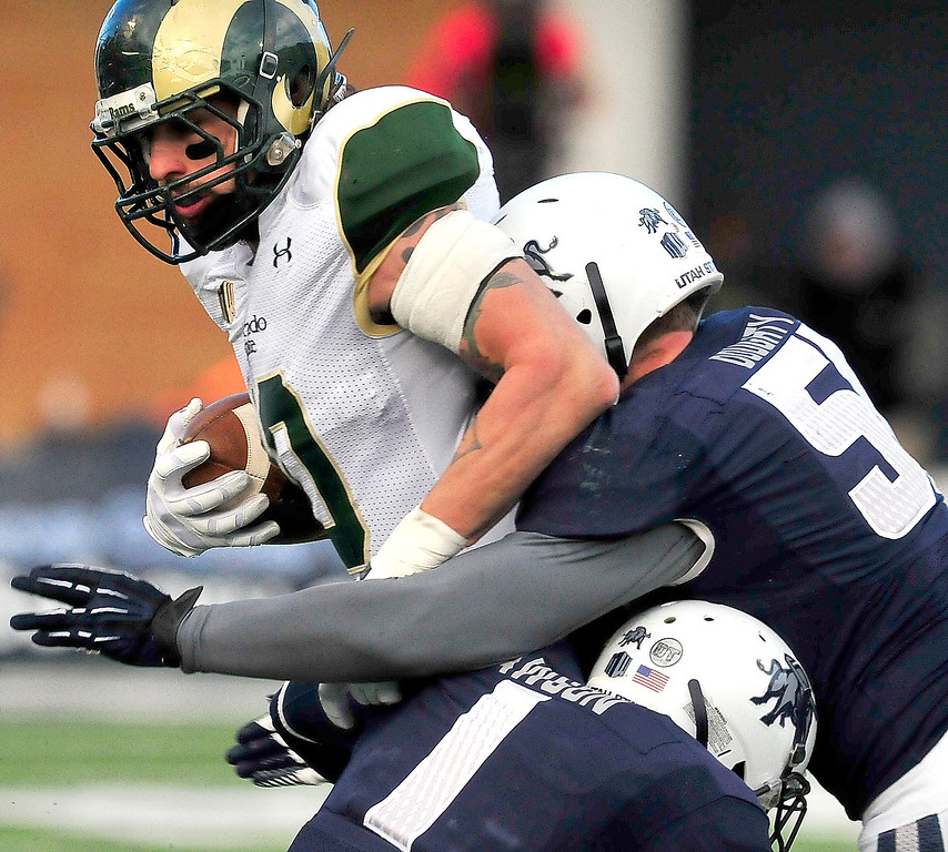 . Colorado State\'s Crockett Gillmore (10) gets tackled by Utah State\'s Nevin Lawson (1) and Jake Doughty (51) during an NCAA college football game, Saturday, Nov. 23, 2013, in Logan, Utah. Utah State won 13-0. (AP Photo/Herald Journal, John Zsiray)