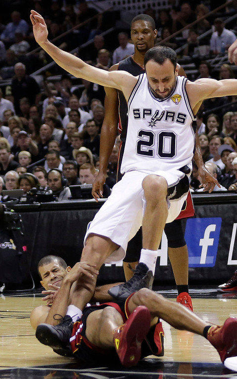 . San Antonio Spurs guard Manu Ginobili (20) tumbles over Miami Heat forward Shane Battier during the first half in Game 5 of the NBA basketball finals on Sunday, June 15, 2014, in San Antonio. (AP Photo/David J. Phillip)