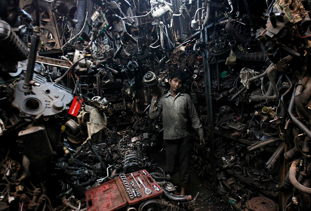 . Abdul Samad, 13, carries a part of a used car engine inside an automobile workshop in Mumbai July 10, 2012. An Indian automobile industry body on Tuesday slightly lowered its car sales growth forecast for the year ending next March, as higher costs and slower economic expansion impinge on demand.  REUTERS/Danish Siddiqui