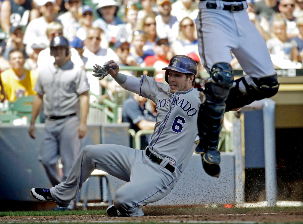 . Colorado Rockies\' Corey Dickerson (6) scores as Milwaukee Brewers catcher Jonathan Lucroy leaps for a throw during the fifth inning of a baseball game Sunday, June 29, 2014, in Milwaukee. (AP Photo/Morry Gash)