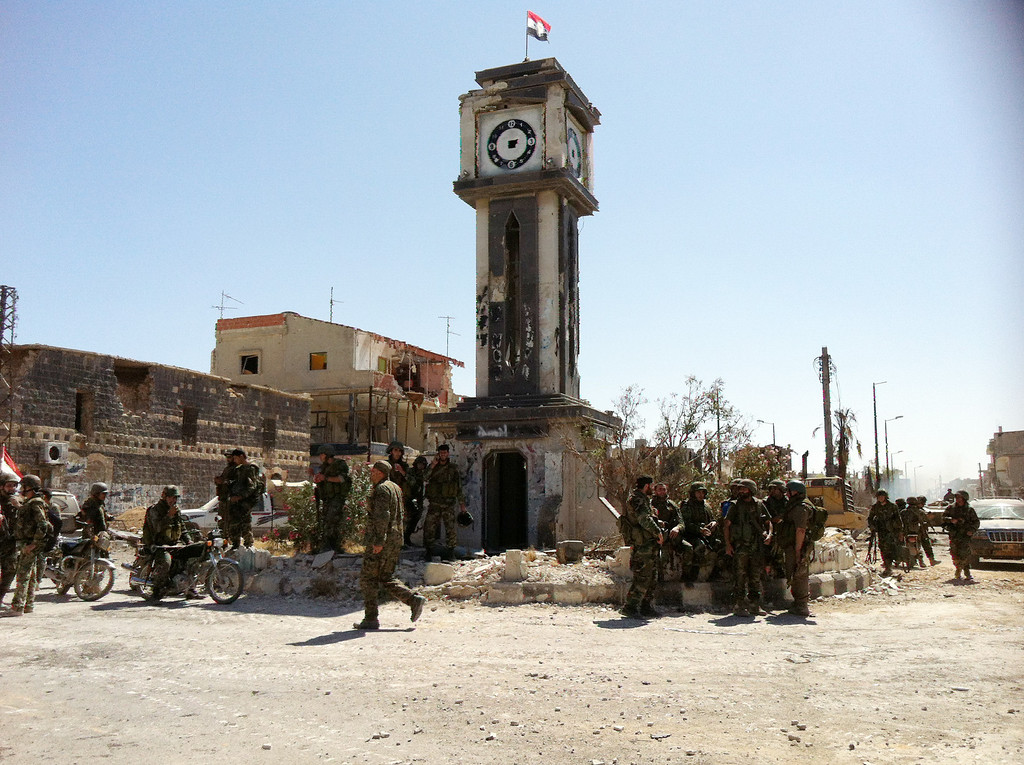 . Syrian army soldiers gather in front of a badly damaged clock tower on top of which flies a Syrian flag on the main square of the city of Qusayr on June 5, 2013 in Syria\'s central Homs province, after the army seized total control of the city and the surrounding region. The Syrian army ousted rebels from the strategic town of Qusayr after a blistering 17-day assault led by Hezbollah fighters, scoring a major battlefield success in a war that has killed at least 94,000 people.   AFP PHOTO / STR-/AFP/Getty Images