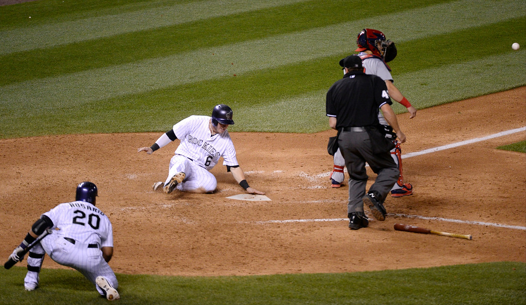 . DENVER, CO - JUNE 24: Colorado Rockies left fielder Corey Dickerson (6) slides at home plate safe on a hit by Colorado Rockies first baseman Justin Morneau (33) in the seventh inning against the St. Louis Cardinals June 24, 2014 at Coors Field. (Photo by John Leyba/The Denver Post)