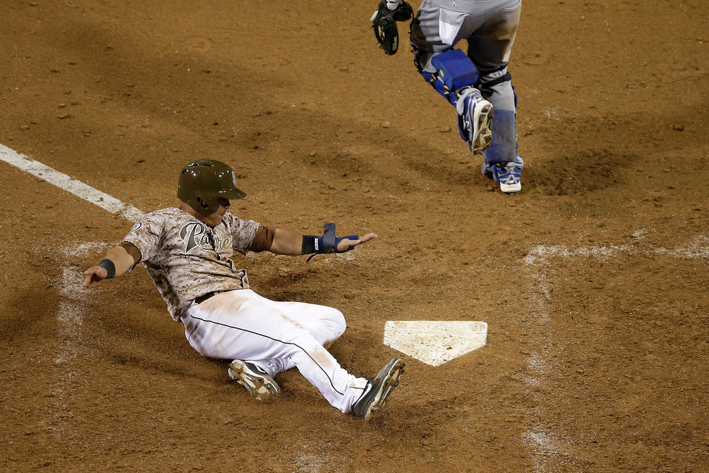 . San Diego Padres\' Everth Cabrera, left, slides in safely to home, scoring off a two-RBI single by Chris Denorfia against the Los Angeles Dodgers during the eighth inning in an opening night baseball game on Sunday, March 30, 2014, in San Diego. (AP Photo/Gregory Bull)