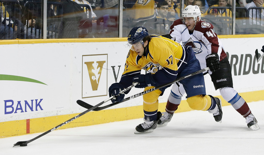 . Nashville Predators right wing Chris Mueller (17) chases the puck with Colorado Avalanche defenseman Tyson Barrie (41) in the second period of an NHL hockey game Tuesday, April 2, 2013, in Nashville, Tenn. (AP Photo/Mark Humphrey)
