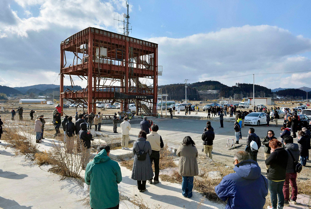 . People observe a moment of silence during a rally at 2:46 p.m. (0546 GMT), the time when the magnitude 9.0 earthquake struck off Japan\'s coast in 2011, near a  tsunami-devastated disaster prevention office building in Minamisanriku town, Miyagi prefecture, March 11, 2013 in this picture provided by Kyodo. Japan honoured the victims of its worst disaster since World War Two on Monday: the March 11, 2011 earthquake, tsunami and nuclear crisis that killed almost 19,000 people and stranded 315,000 evacuees, including refugees who fled radiation from the devastated Fukushima atomic plant. Mandatory Credit. REUTERS/Kyodo