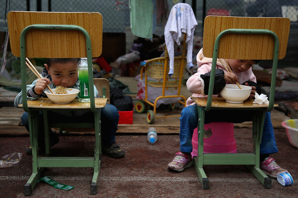 . Two earthquake survivors eat instant noodles outside the tent in a middle school on April 22, 2013 in Baoxing county of Ya An, China.  A magnitude 7 earthquake hit China\'s Sichuan province on April 20 claiming over 190 lives and injuring thousands.  (Photo by Feng Li/Getty Images)
