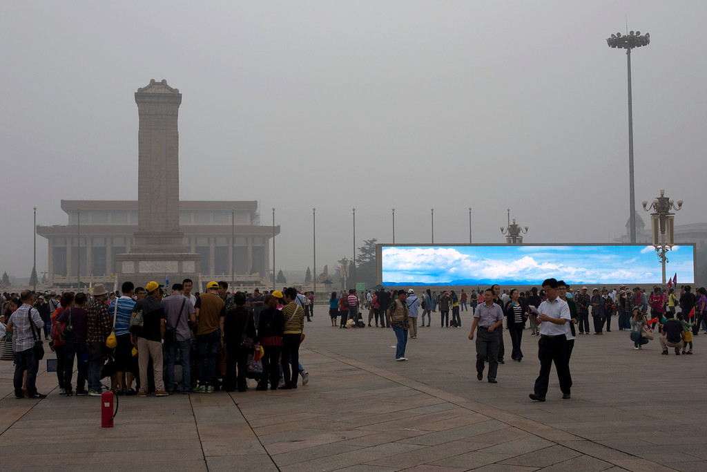 ". In this photo taken on Sept. 13, 2013 tourists visit Tiananmen Square on a hazy day while an electronic screen shows a blue sky and white clouds as part of a propaganda video in Beijing, China. Chinaís tourism industry has grown at a fast pace since the country began free market-style economic reforms three decades ago. However, it\'s latest tourism slogan ""Beautiful China\"" has been derided as particularly inept at a time when record-busting smog has drawn attention to the environmental and health costs of Chinaís unfettered industrialization. Some point to unsophisticated marketing as an explanation.   (AP Photo/Alexander F. Yuan)"