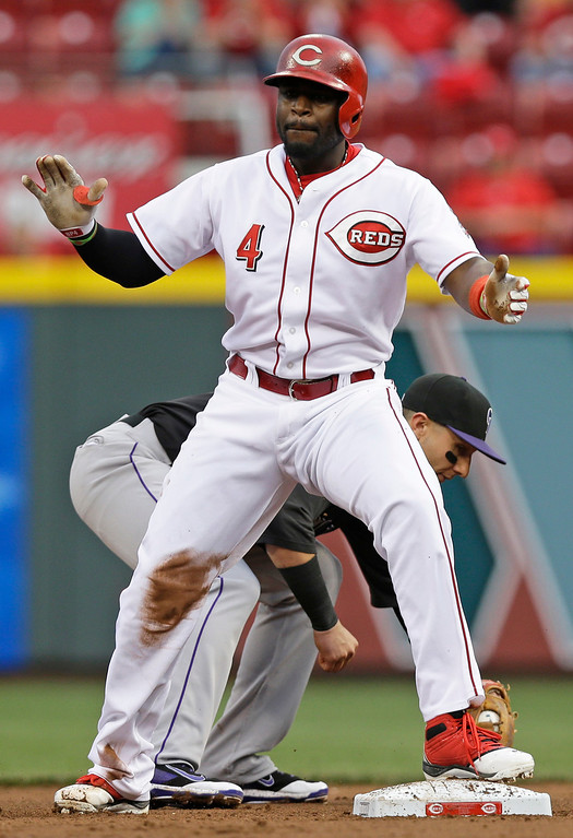 . Cincinnati Reds\' Brandon Phillips (4) claps after hitting a double in the third inning of a baseball game against the Colorado Rockies, Friday, May 9, 2014, in Cincinnati. Rockies shortstop Troy Tulowitzki catches the late throw. (AP Photo/Al Behrman)