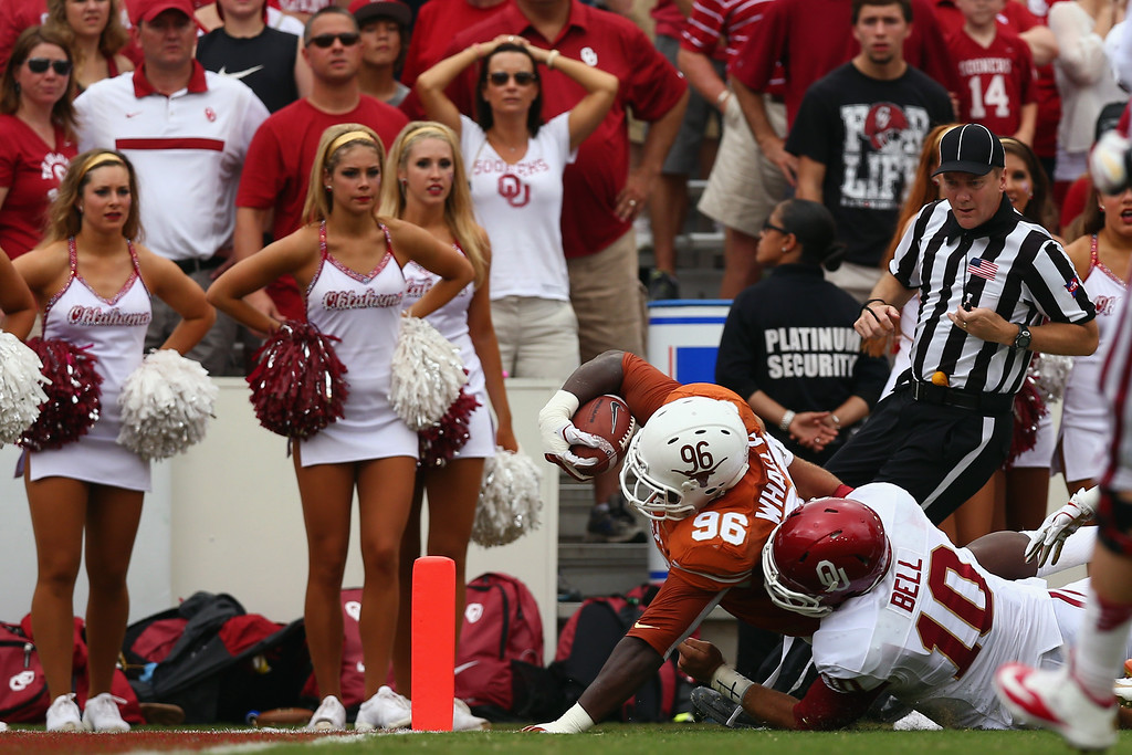 . Chris Whaley #96 of the Texas Longhorns carries the ball into the end zone turnover score against Blake Bell #10 of the Oklahoma Sooners after Whaley intercepted the ball in the first quarter at the Cotton Bowl on October 12, 2013 in Dallas, Texas.  (Photo by Tom Pennington/Getty Images)